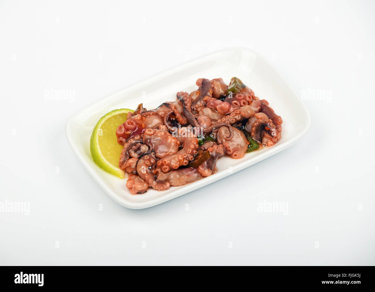Seafood octopus cuttlefish marinated salad snack with souse on white dish plate over white background, high angle - Stock Image