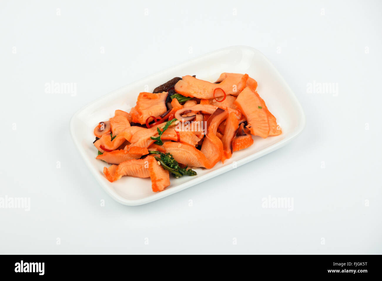 Seafood calamari squid, seaweeds and chili marinated salad snack with souse on white dish plate over white background, - Stock Image