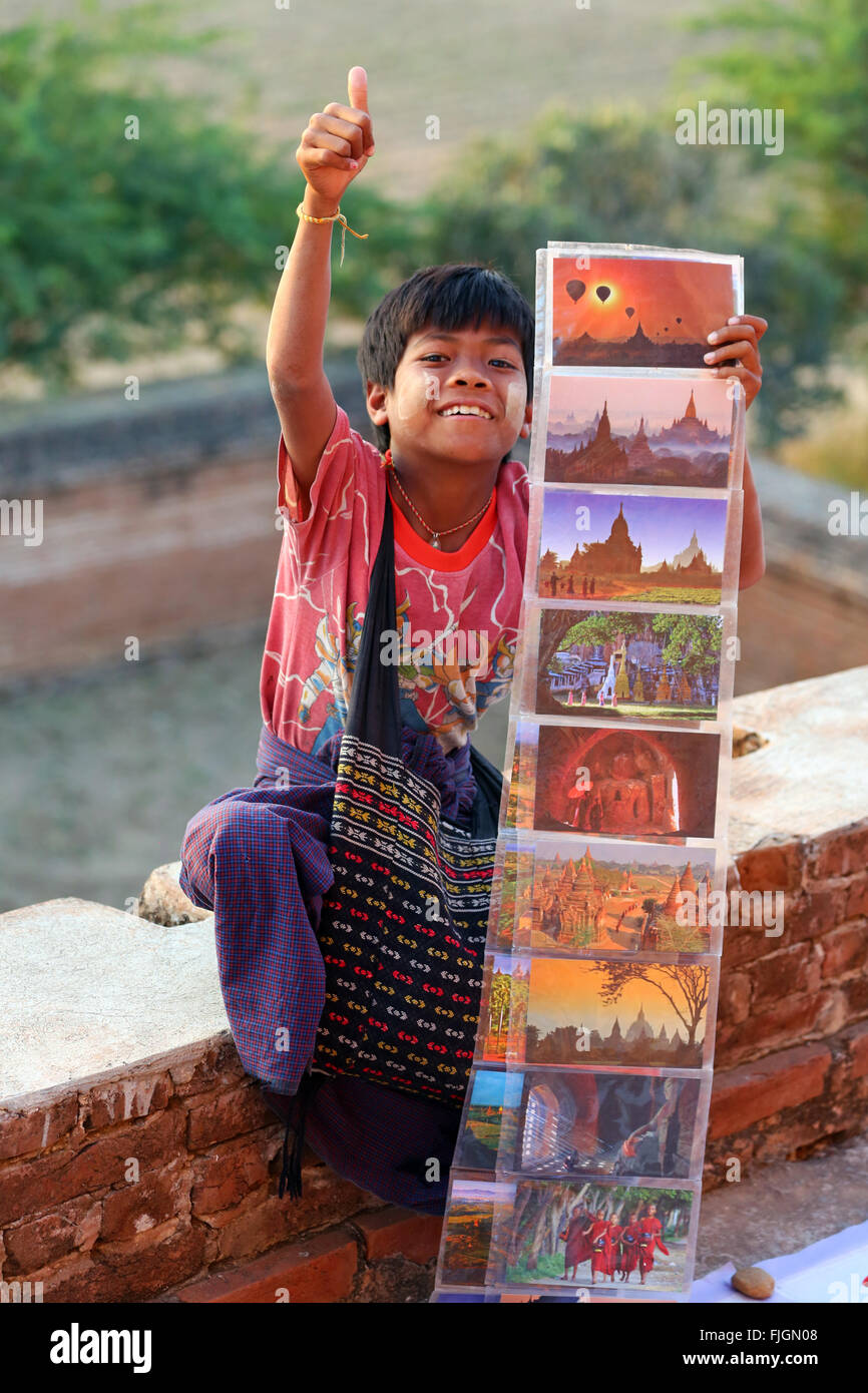 Boy selling postcards to tourists at North Guni Temple Pagoda on the Plain of Bagan, Bagan, Myanmar (Burma) - Stock Image