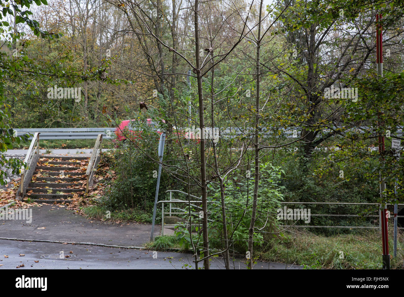neglected scrubby area at city periphery with stair and entrance to pedestrian underpass, arterial road, red car - Stock Image