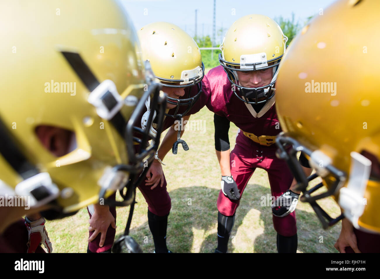 American Football players at strategy huddle - Stock Image