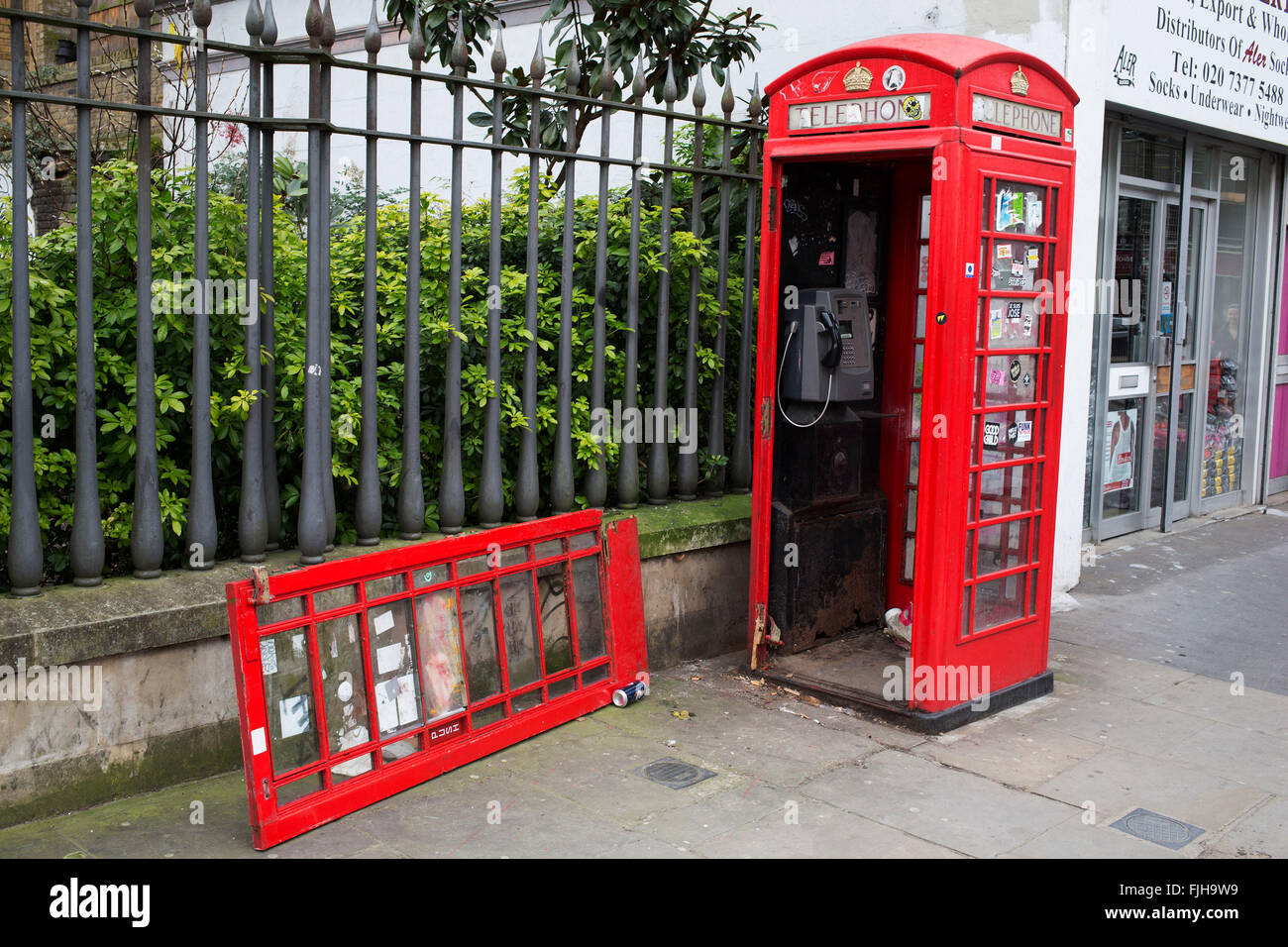 Broken traditional red telephone call box. London, UK. Rarely used nowadays, these old red phone boxes are often - Stock Image