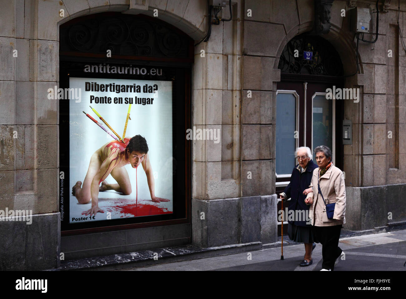 People walking past a poster in window protesting against bullfighting, Casco Viejo, Bilbao, Basque Country, Spain - Stock Image