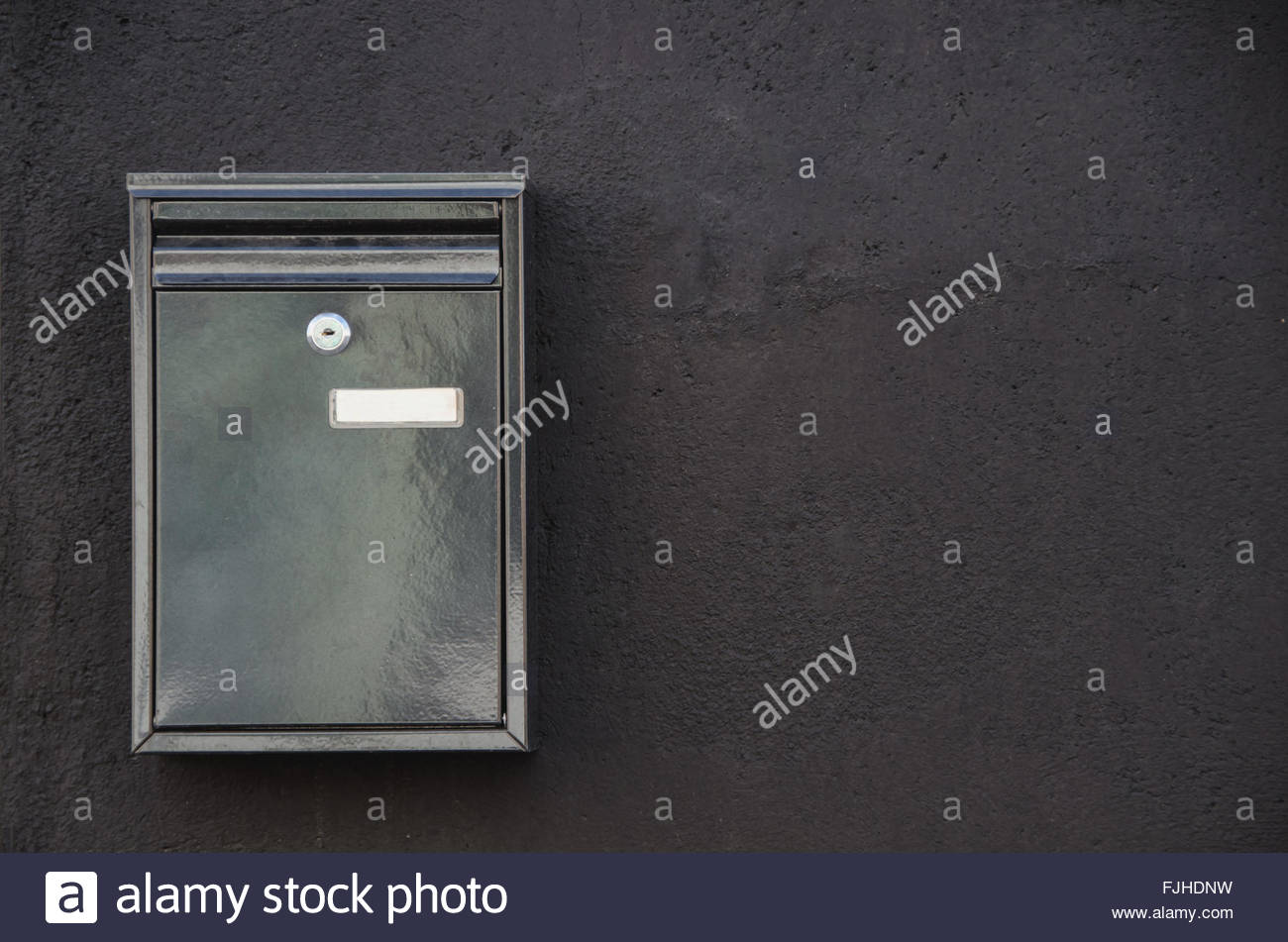 Close Up Of Metal Mailbox Hanging On Black Cement Wall With Keyhole