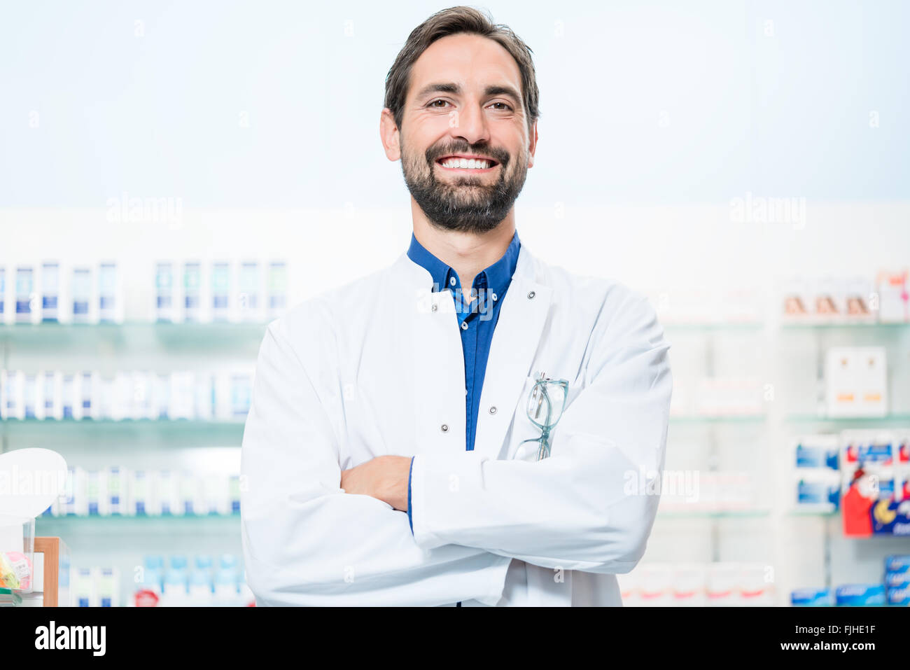 Apothecary in pharmacy standing at shelf with drugs - Stock Image