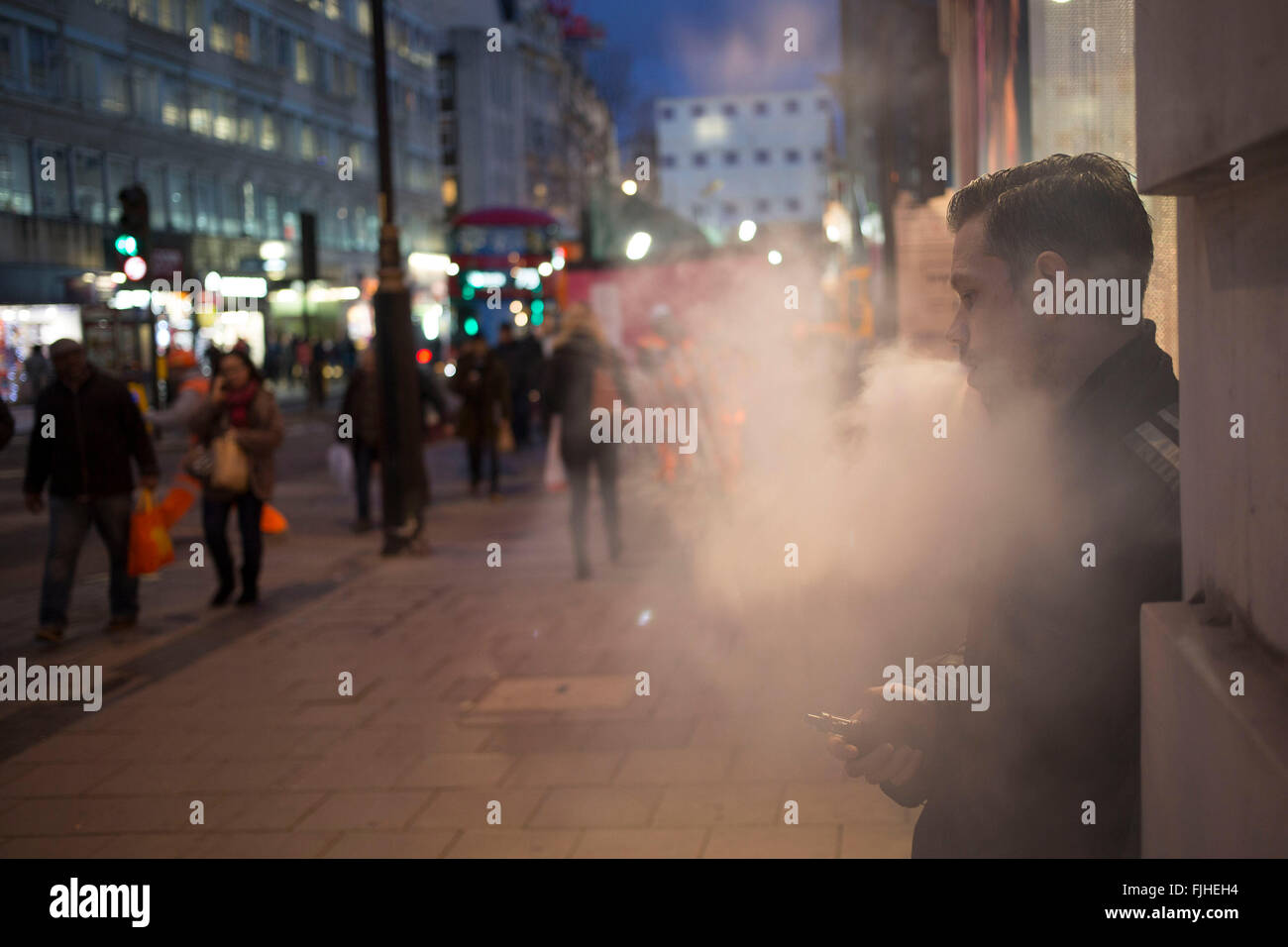 Man smoking a vaporizer on Oxford Street in central London, UK. Britiains busiest shopping district. Electronic - Stock Image