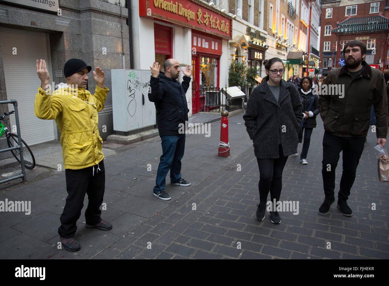 Members of Falun Gong or Falun Dafa meditating on Gerrard Street in central London, UK. Falun gong claim the following: - Stock Image