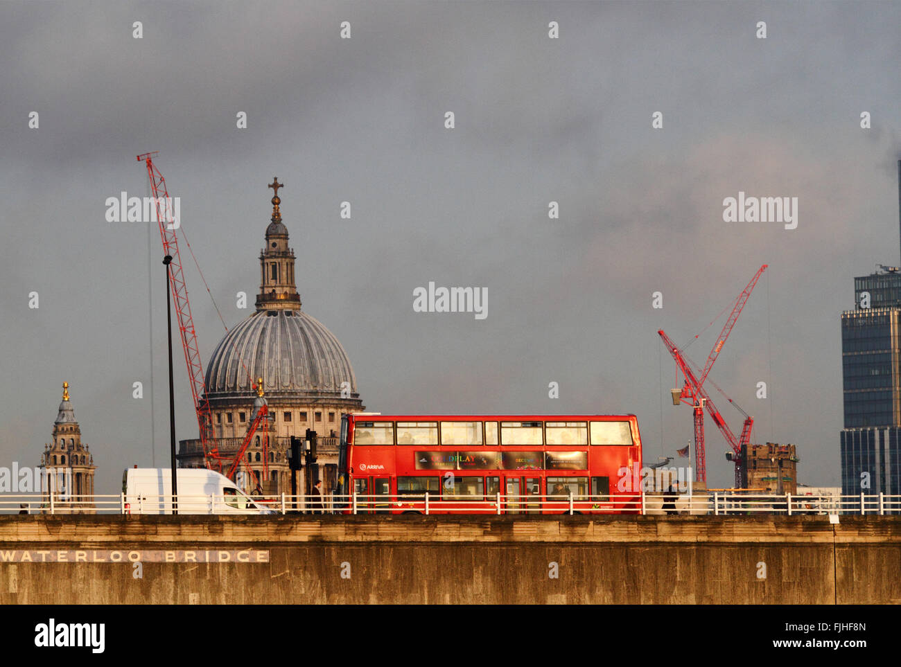 Red double deck bus crossing Waterloo Bridge, St Paul's Cathedral dome in background, London, England. - Stock Image