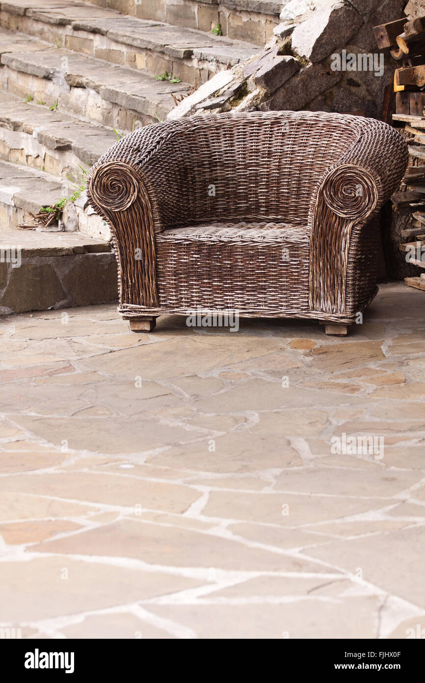 Old braided wicker chair with signs of wear Stock Photo