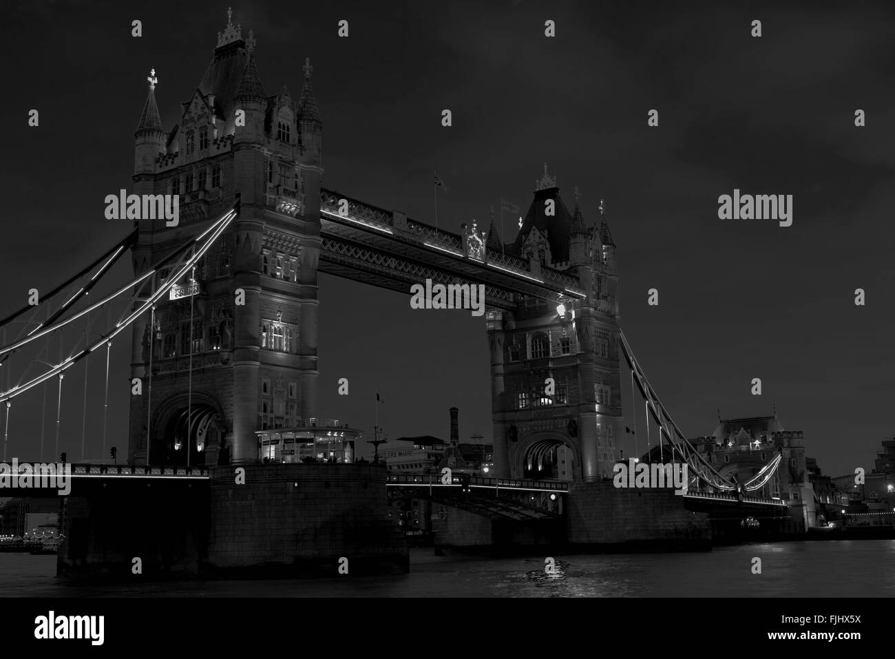 Tower Bridge illuminated at night, black and white image - Stock Image