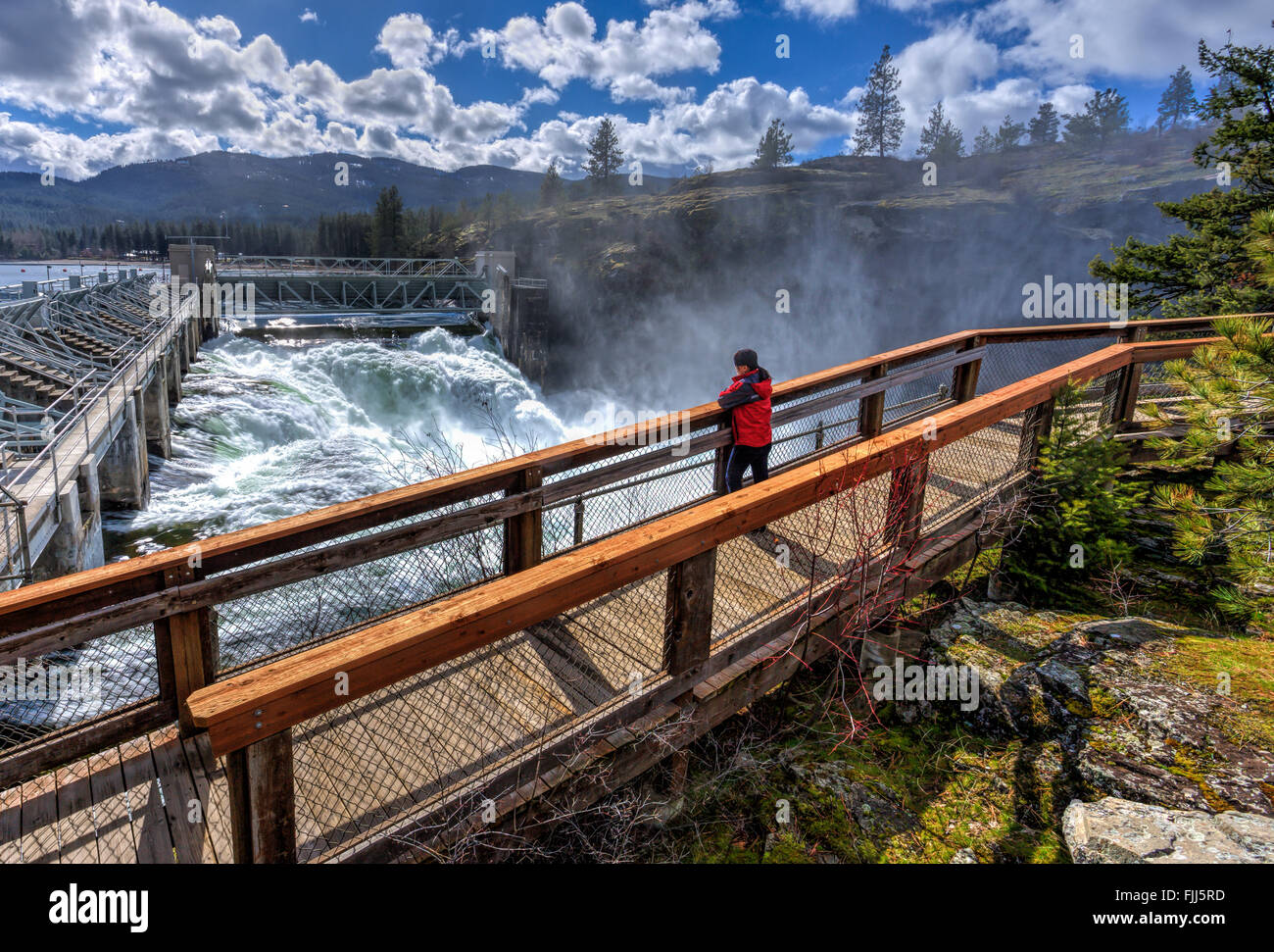 A woman looks out at the rushing water at the Post Falls Dam in Idaho. - Stock Image