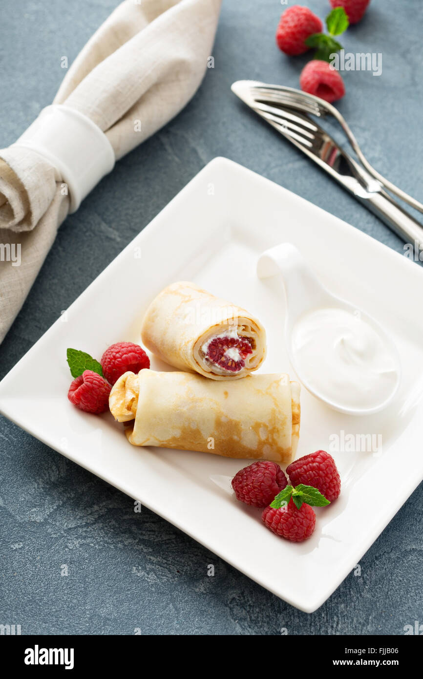 Crepes filled with cottage cheese and raspberry - Stock Image