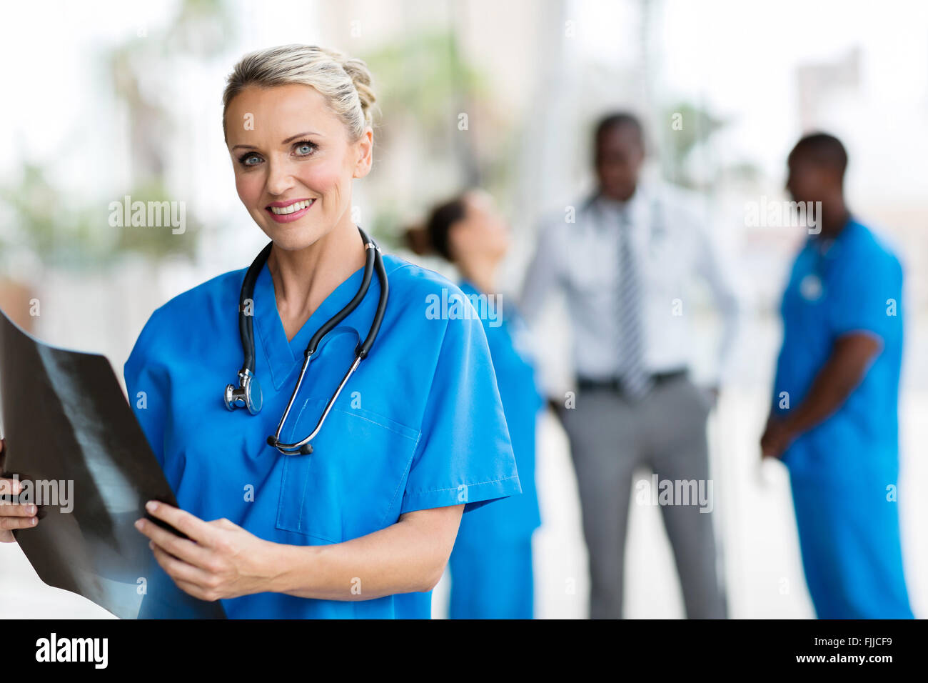 beautiful female doctor holding CT scan in office - Stock Image