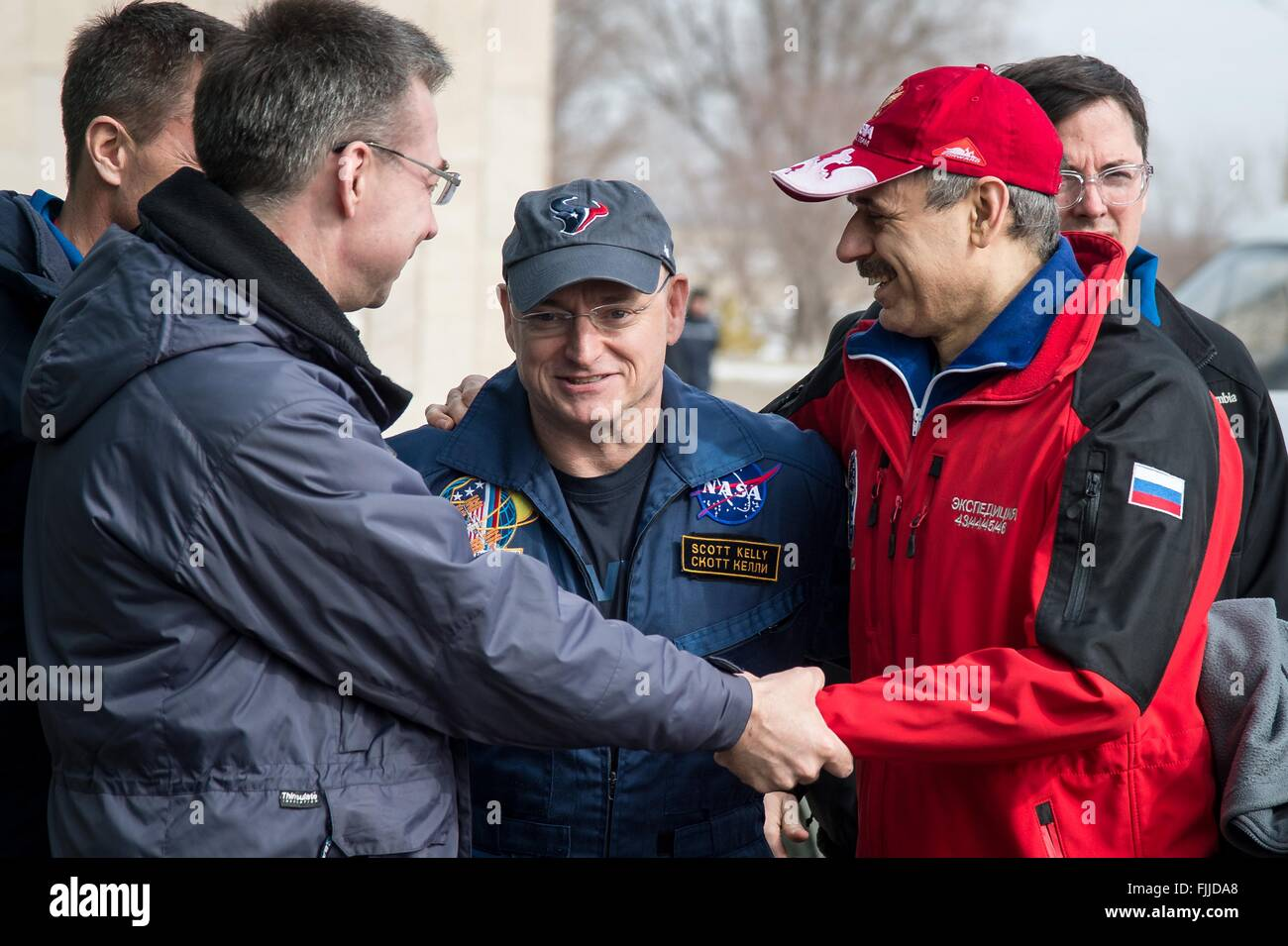 American astronaut Scott Kelly, center, is embraced by crew member Russian cosmonaut Mikhail Kornienko on arrival - Stock Image