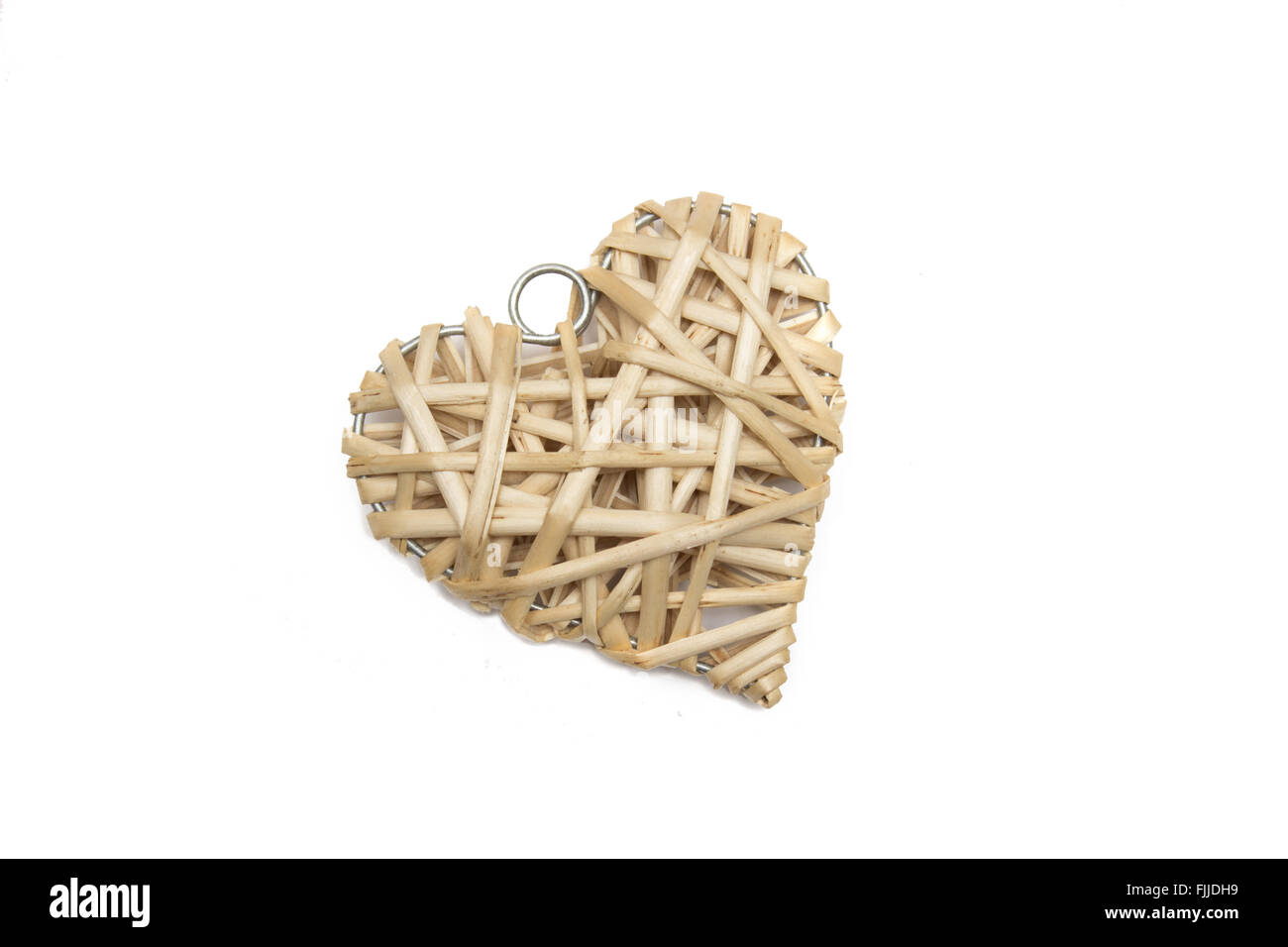 Straw heart on a white background - Stock Image