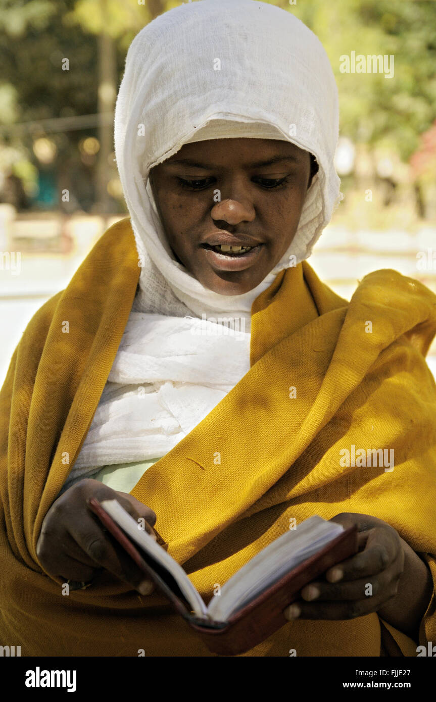 Nun reading a book outside the new Church of Our Lady Mary of Zion in Axum (or Aksum), Tigray Region, Ethiopia Stock Photo
