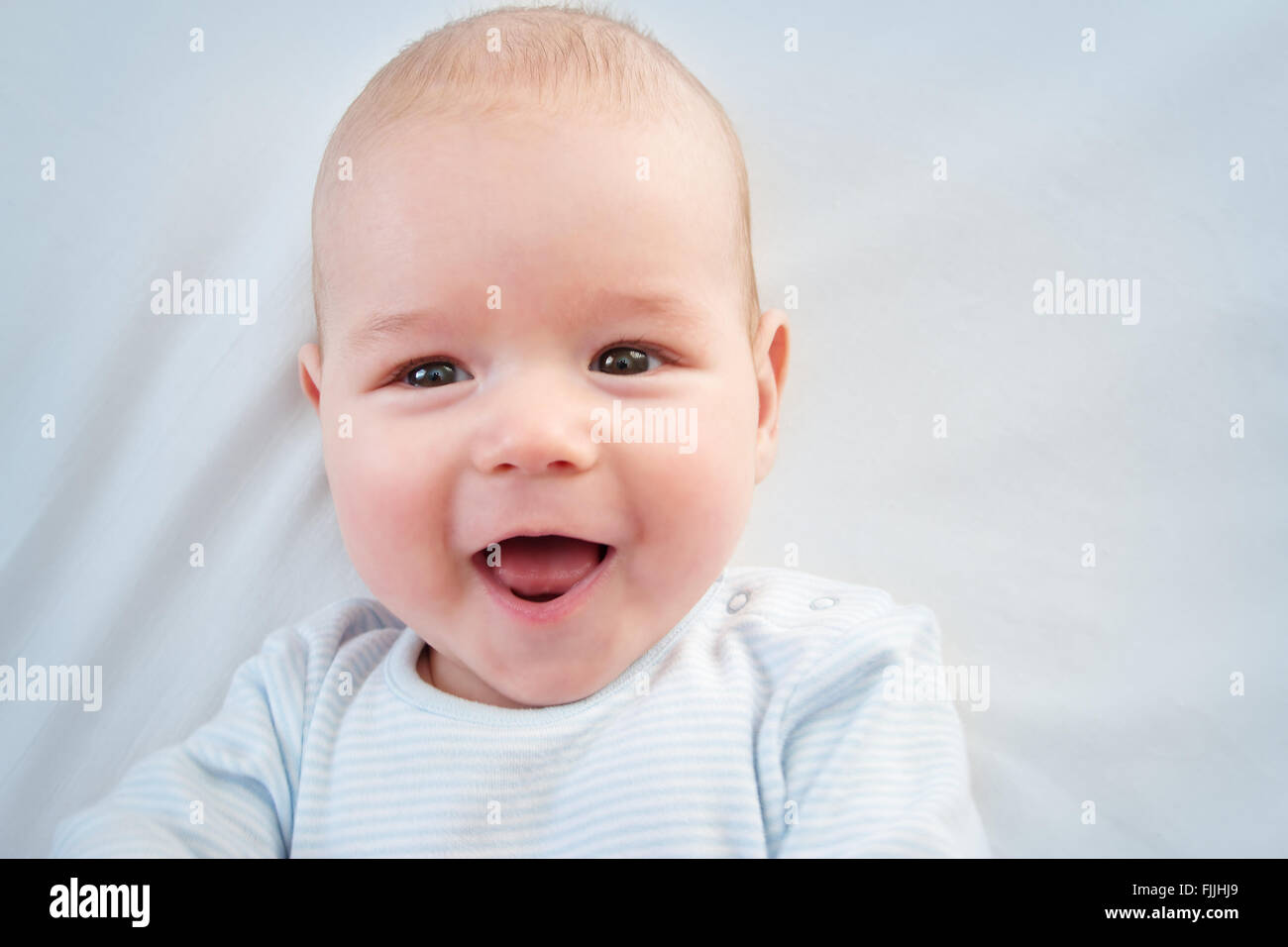 three month old baby lying in bed - Stock Image