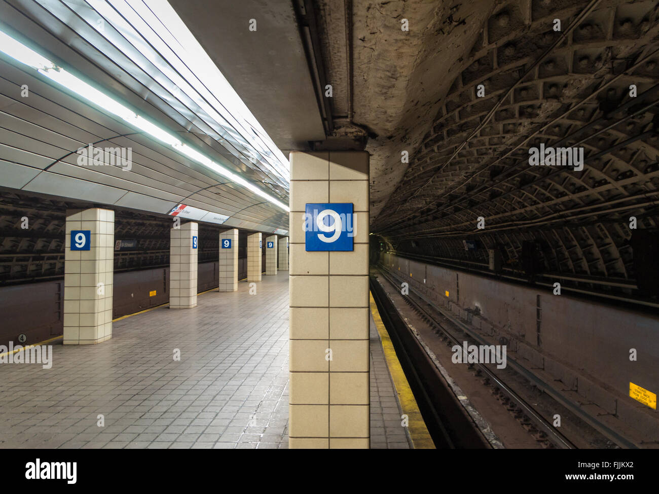 Interior of 9th Street PATH underground subway station in New York City looking along the platform and train tracks - Stock Image