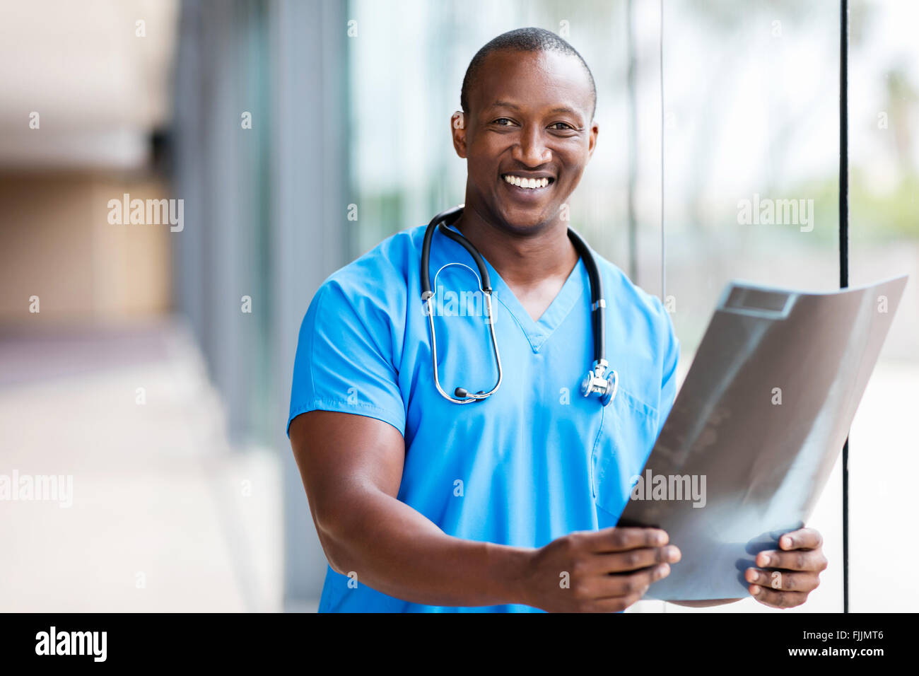 professional African medical doctor holding CT scan - Stock Image