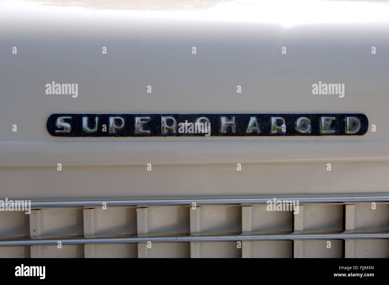 Art deco style 'Super-charged' name plate on a 1930's Auburn car - Stock Image
