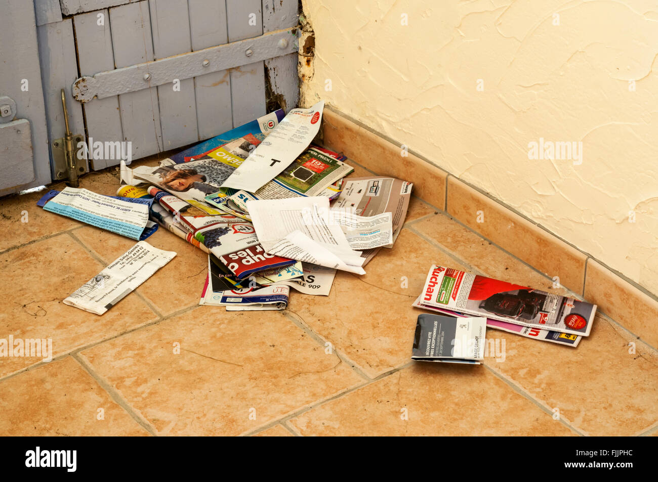 Junk mail on floor behind door of an empty property. - Stock Image