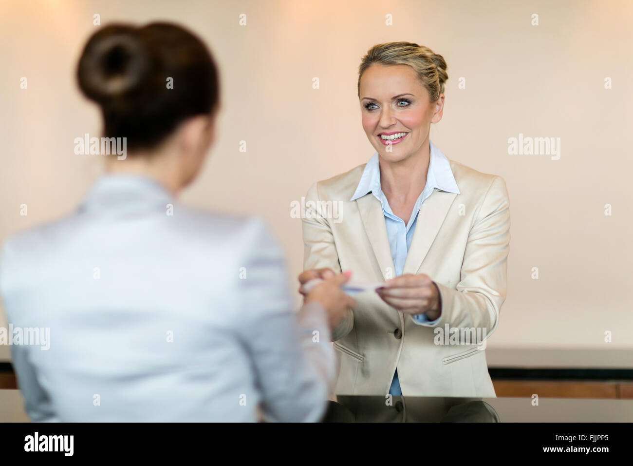 friendly hotel receptionist handing over key to customer - Stock Image