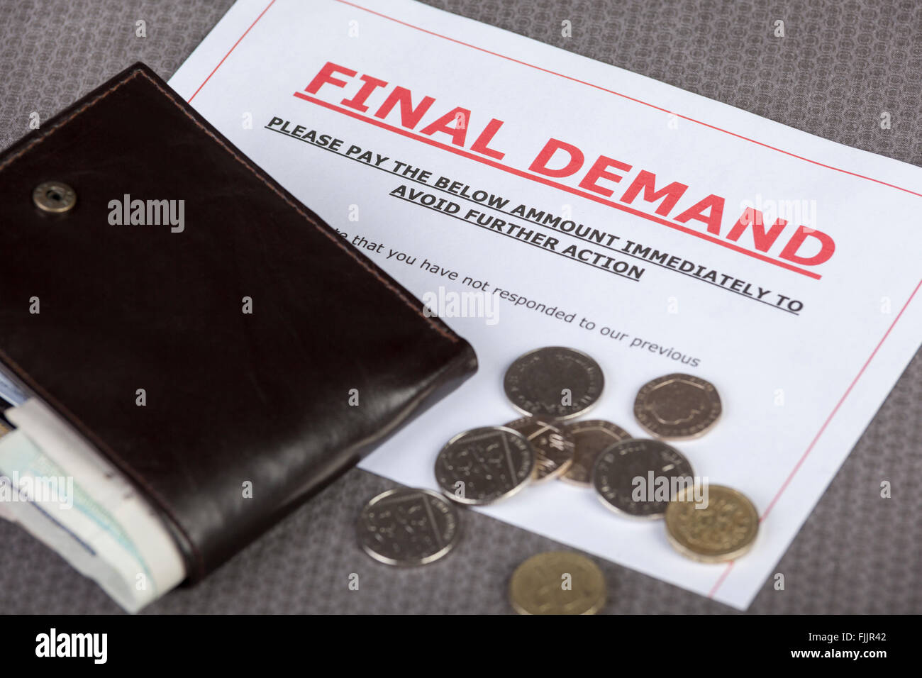 Final demand laying on a table with some loose cash and wallet - Stock Image
