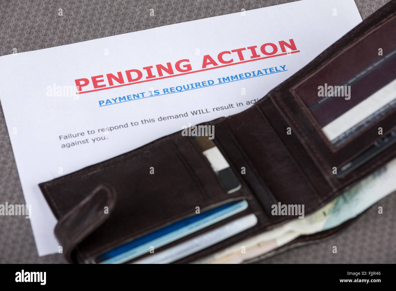 Open wallet with credit cards and cash laying across a final demand letter - Stock Image