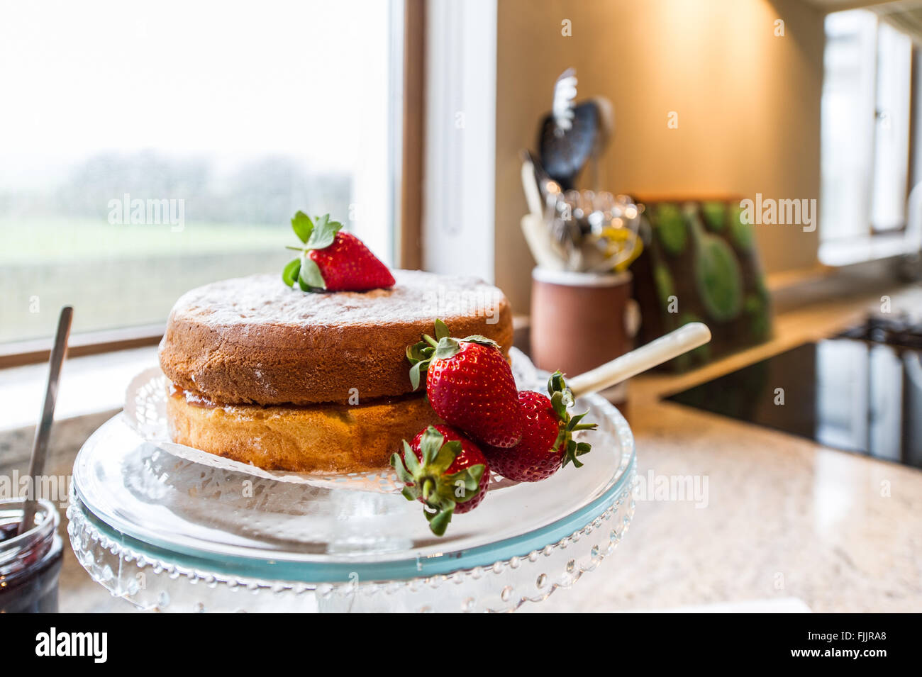 Home made sponge cake with strawberries on a stand in a domestic kitchen. - Stock Image