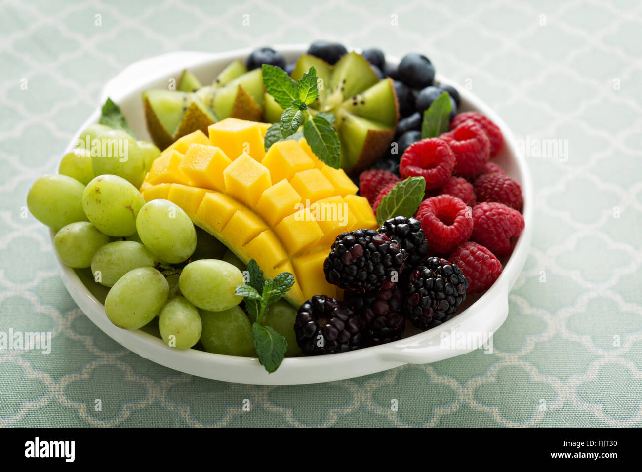 Fruit plate with berries, mango and kiwi - Stock Image