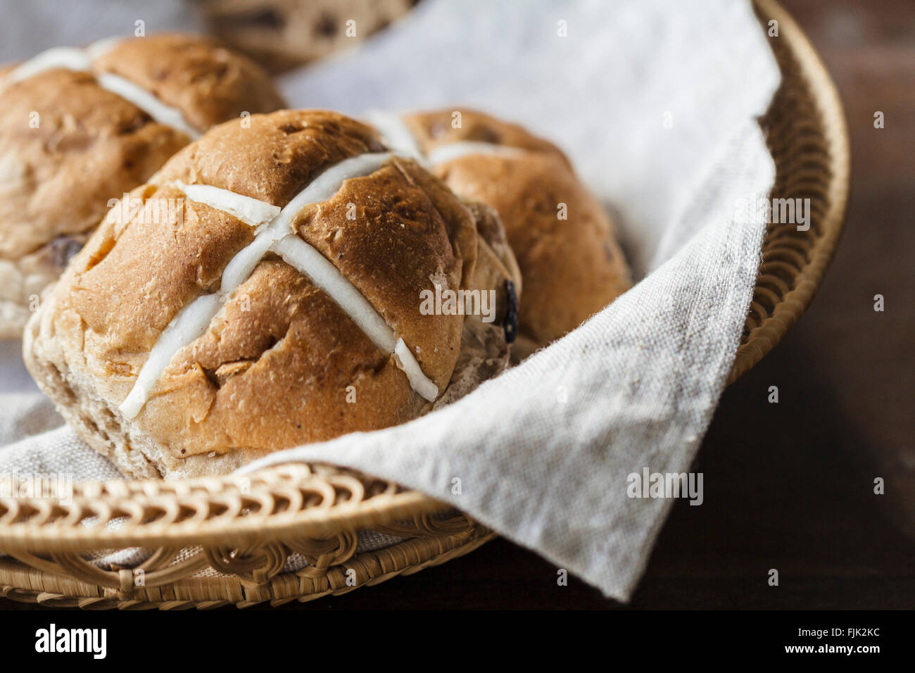 Three Easter hot cross buns in a basket on a rustic wooden table - Stock Image