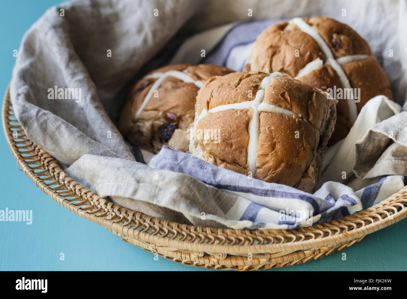 Three Easter hot cross buns in a basket with blue and grey linen cloth - Stock Image