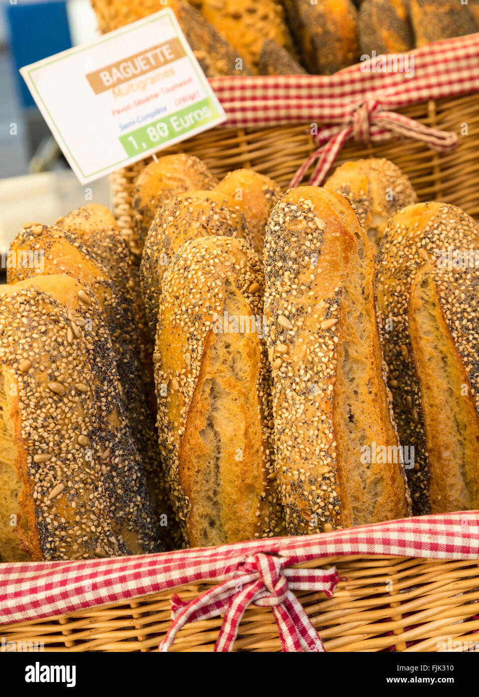 Typical French bread seeded baguettes displayed in wicker baskets at a local street market, Paris, France - Stock Image