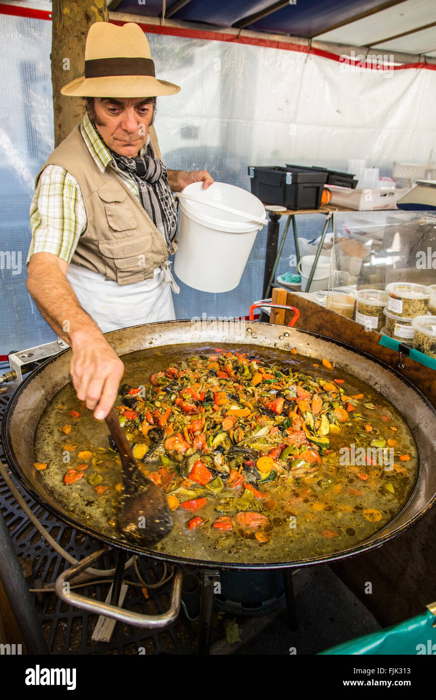 Food vendor cooking traditional Spanish paella in a giant pan at a street market, Paris, France - Stock Image