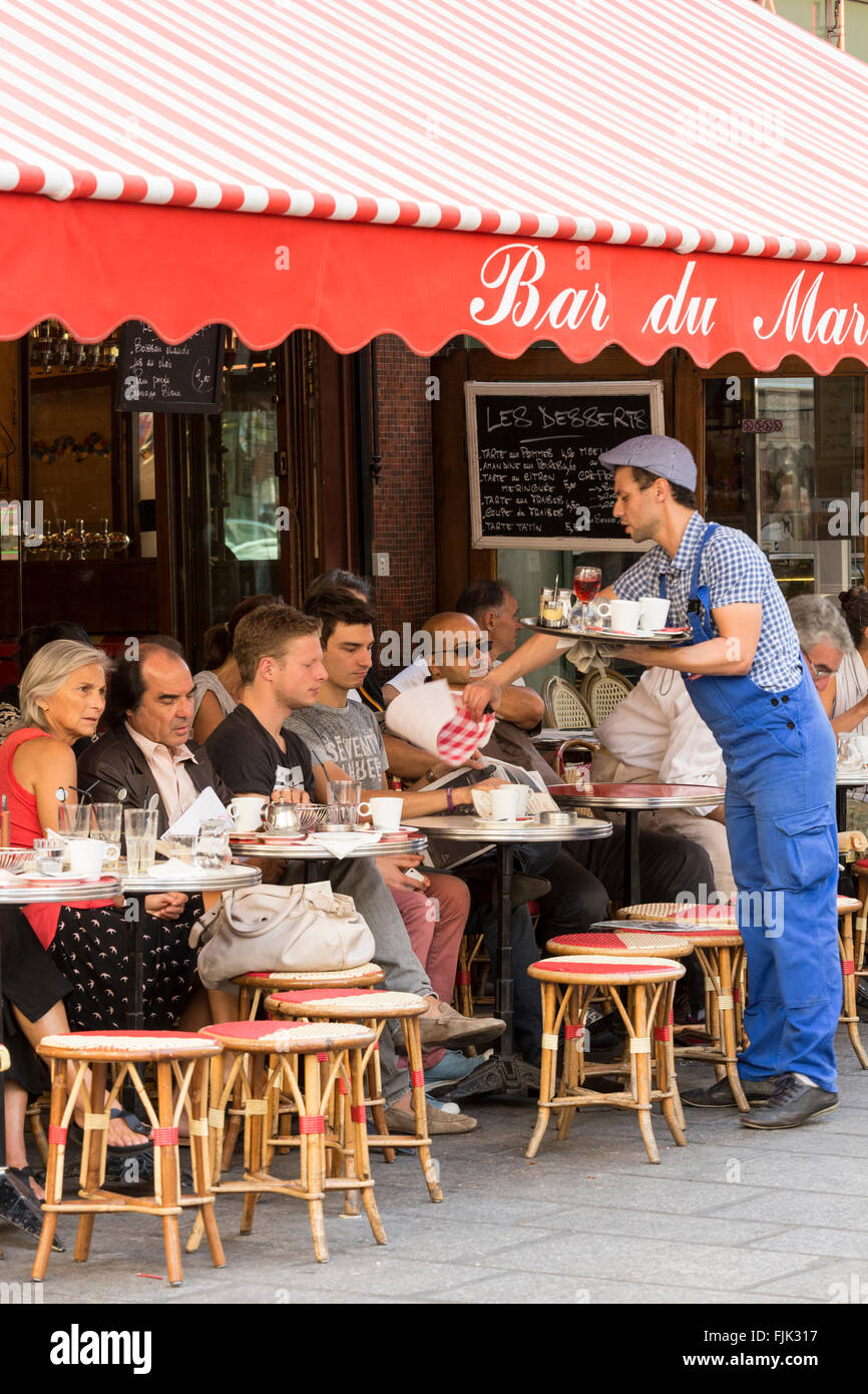 Waiter serving customers at Bar du Marche, a typical sidewalk cafe in the fashionable Saint Germain district, Paris, - Stock Image