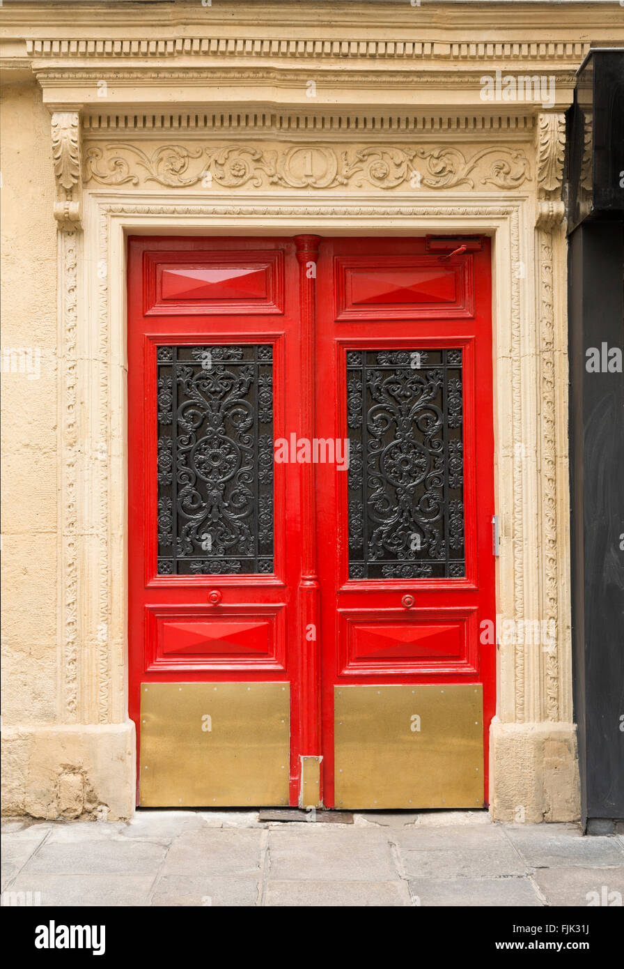 Typical architectural detail of red doors with wrought iron panels, Paris, France - Stock Image