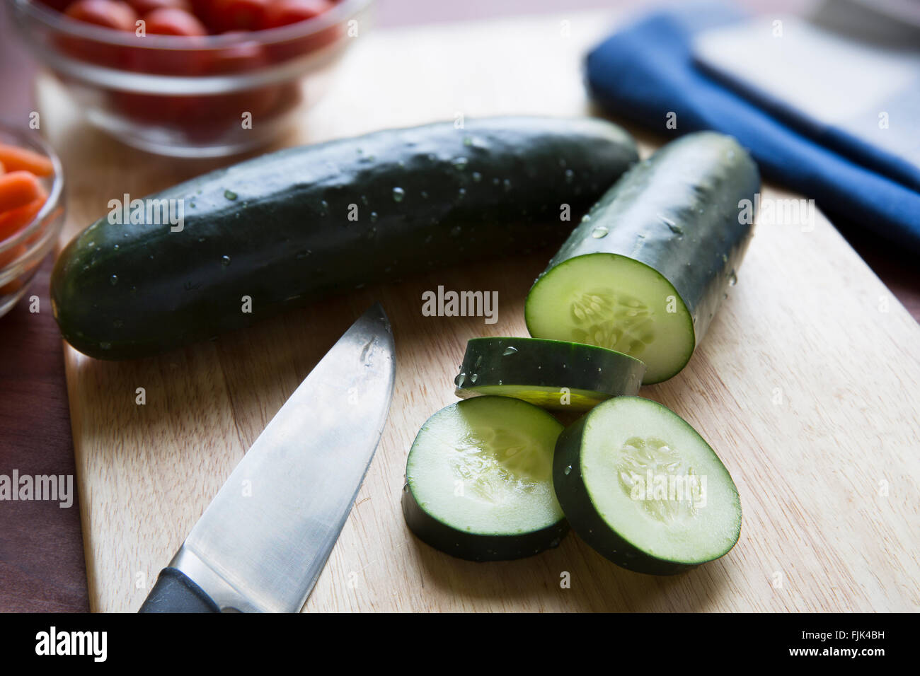 Cucumbers and knife on cutting board. - Stock Image