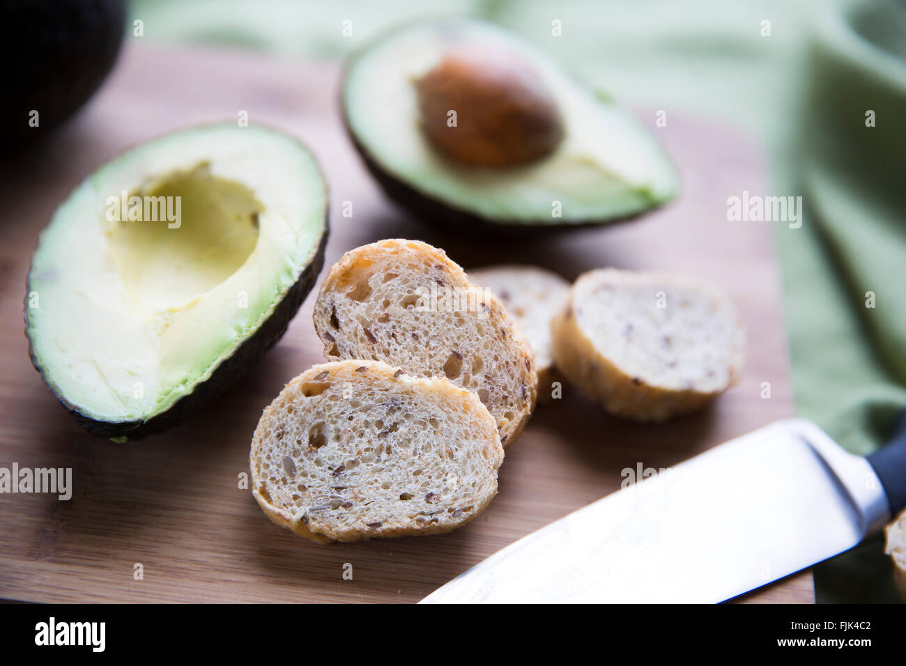 Fresh avocado cut in half and small slices of bread for making avocado toast. - Stock Image