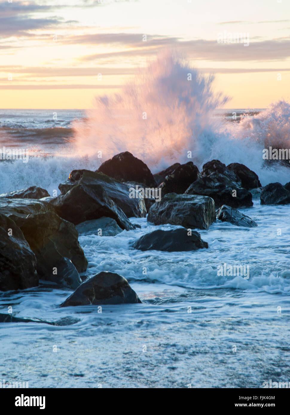 Waves from the Tasman Sea crashing on rocks at sunset, Hokitika, South Island, New Zealand - Stock Image
