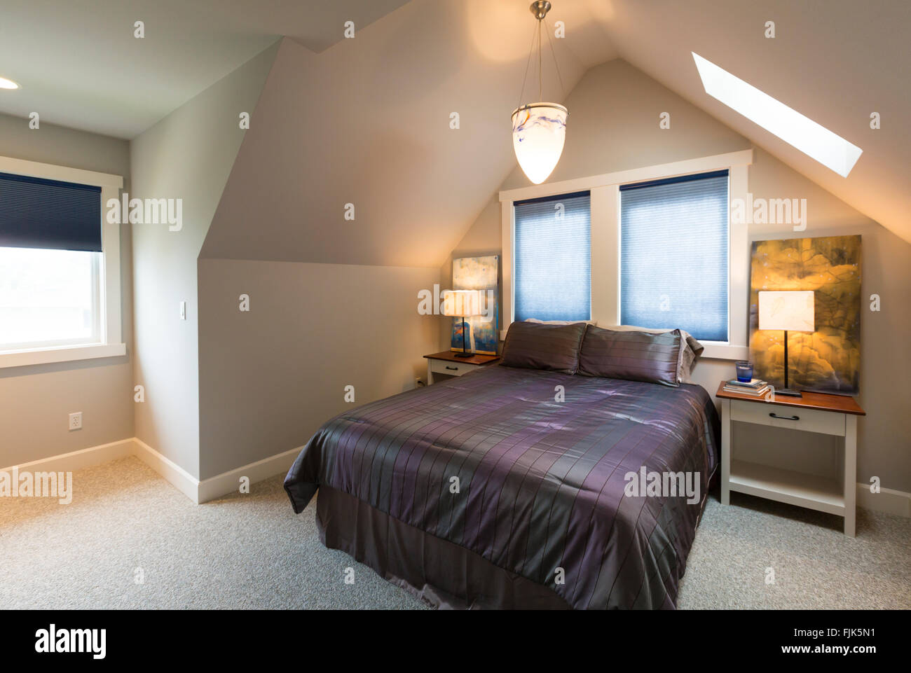 Bedroom with bed, bedside tables, vaulted ceiling, windows with window coverings, artwork and accent lighting in Stock Photo