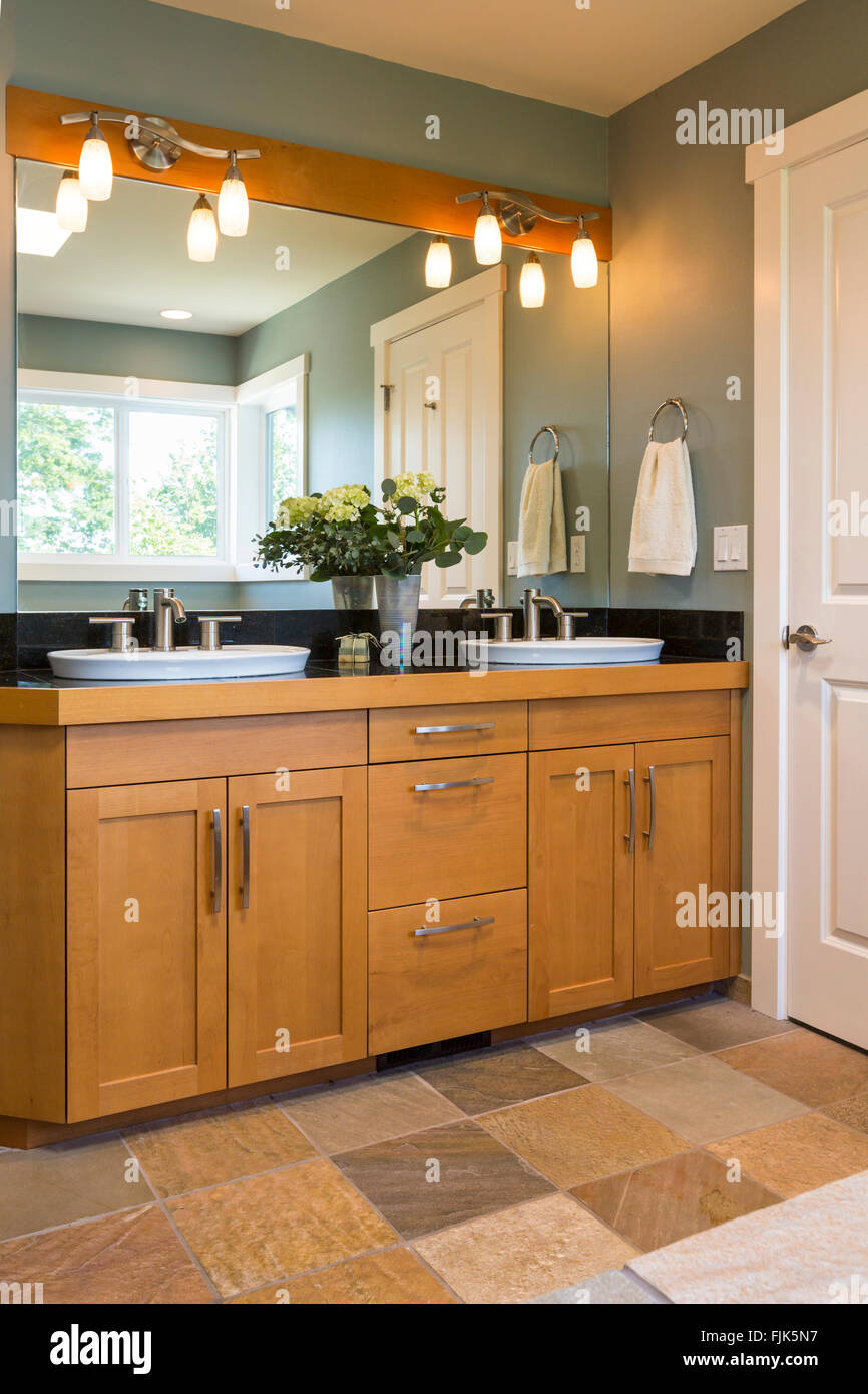 Bathroom vanity with wood cabinets, double sinks, slate tile floors and accent lighting in contemporary upscale - Stock Image