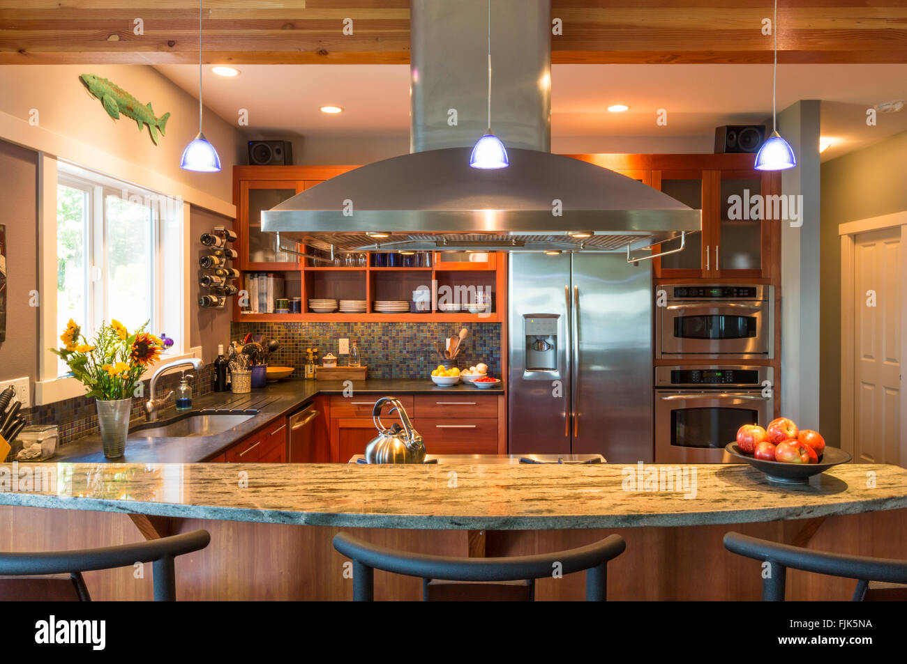 Breakfast bar in contemporary upscale home kitchen with granite countertops, stainless steel appliances and accent - Stock Image