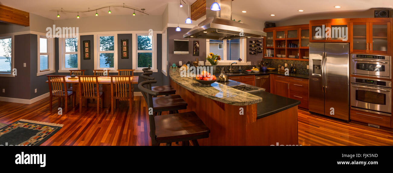 Panoramic view of open plan kitchen & dining area in upscale contemporary home  with wood floors, view windows - Stock Image