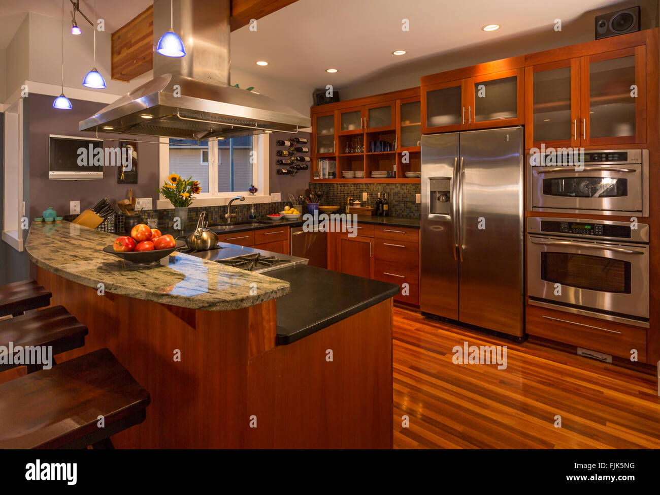 Contemporary upscale home kitchen interior with wood cabinets & floors, granite countertops, stainless steel - Stock Image