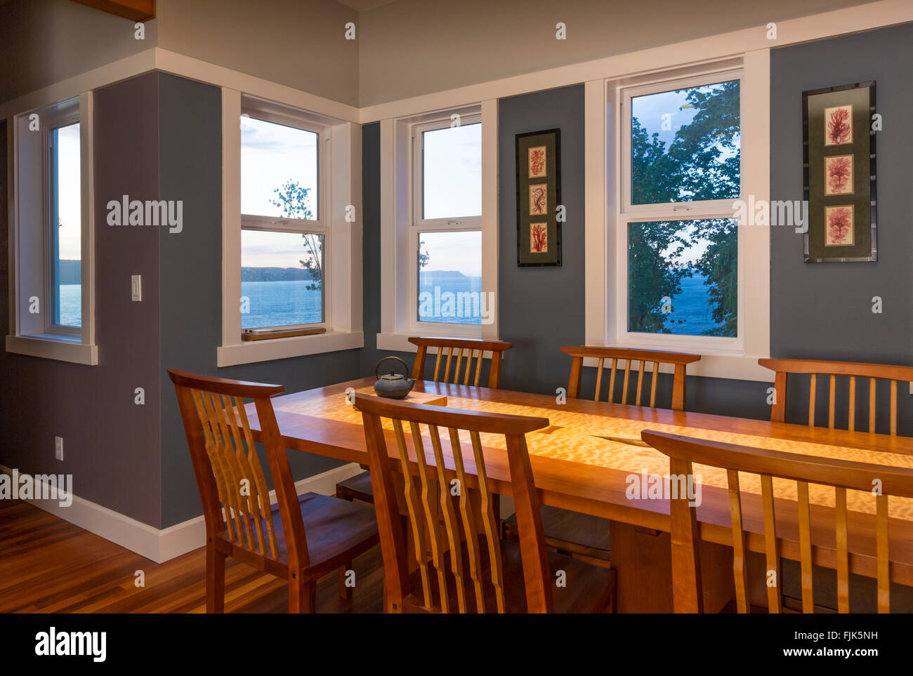 Dining area with wood table and chairs and view windows in contemporary upscale home interior - Stock Image