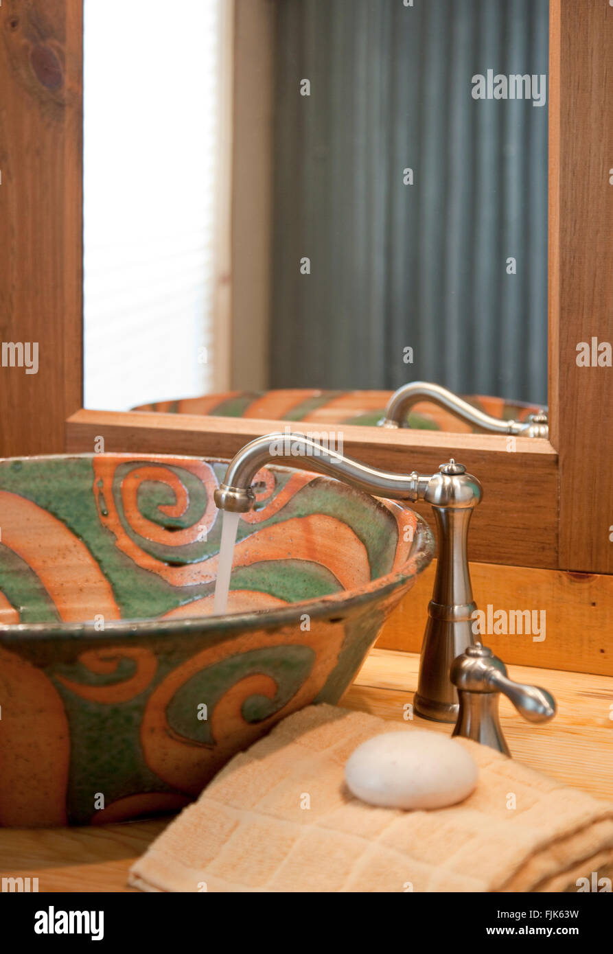 Running water from a stainless steel faucet in a handmade ceramic sink, hand towel and mirror in a creative home - Stock Image