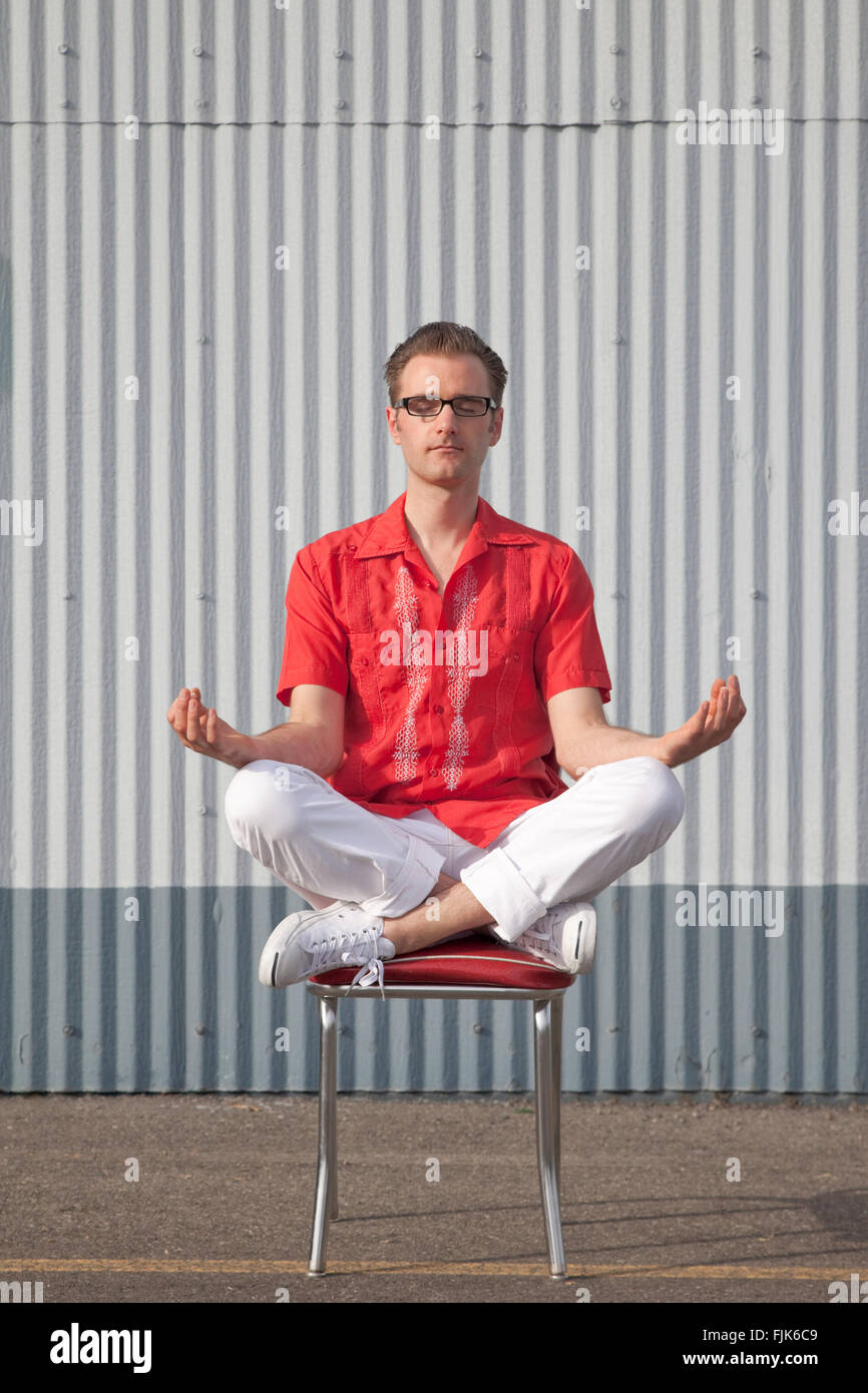 Hipster man in retro clothing sitting and meditating in yoga position on chair. American geek chic. - Stock Image