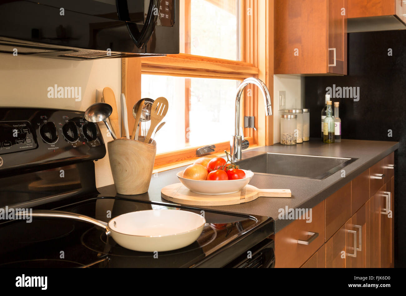 Electric stove, wood cabinets, laminate countertop and stainless steel sink in contemporary home kitchen interior. - Stock Image