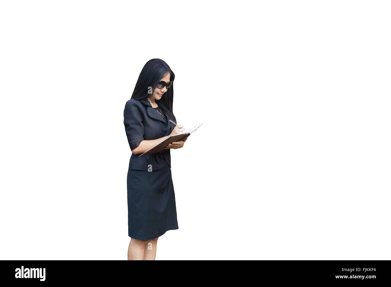 Isolated Asian business women wearing sunglass standing and writing down on note book on white background - Stock Image