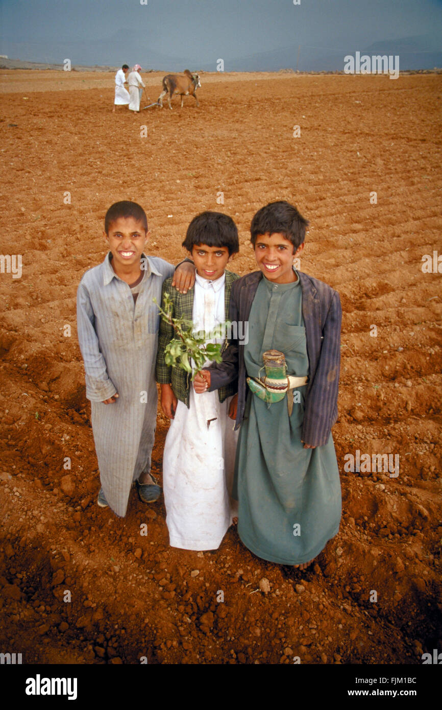Three boys, in Yemen, together while their parents are working at the background - Stock Image